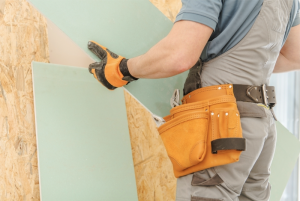 builder lifting drywood for home construction