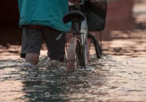 man walking through flood water with bike
